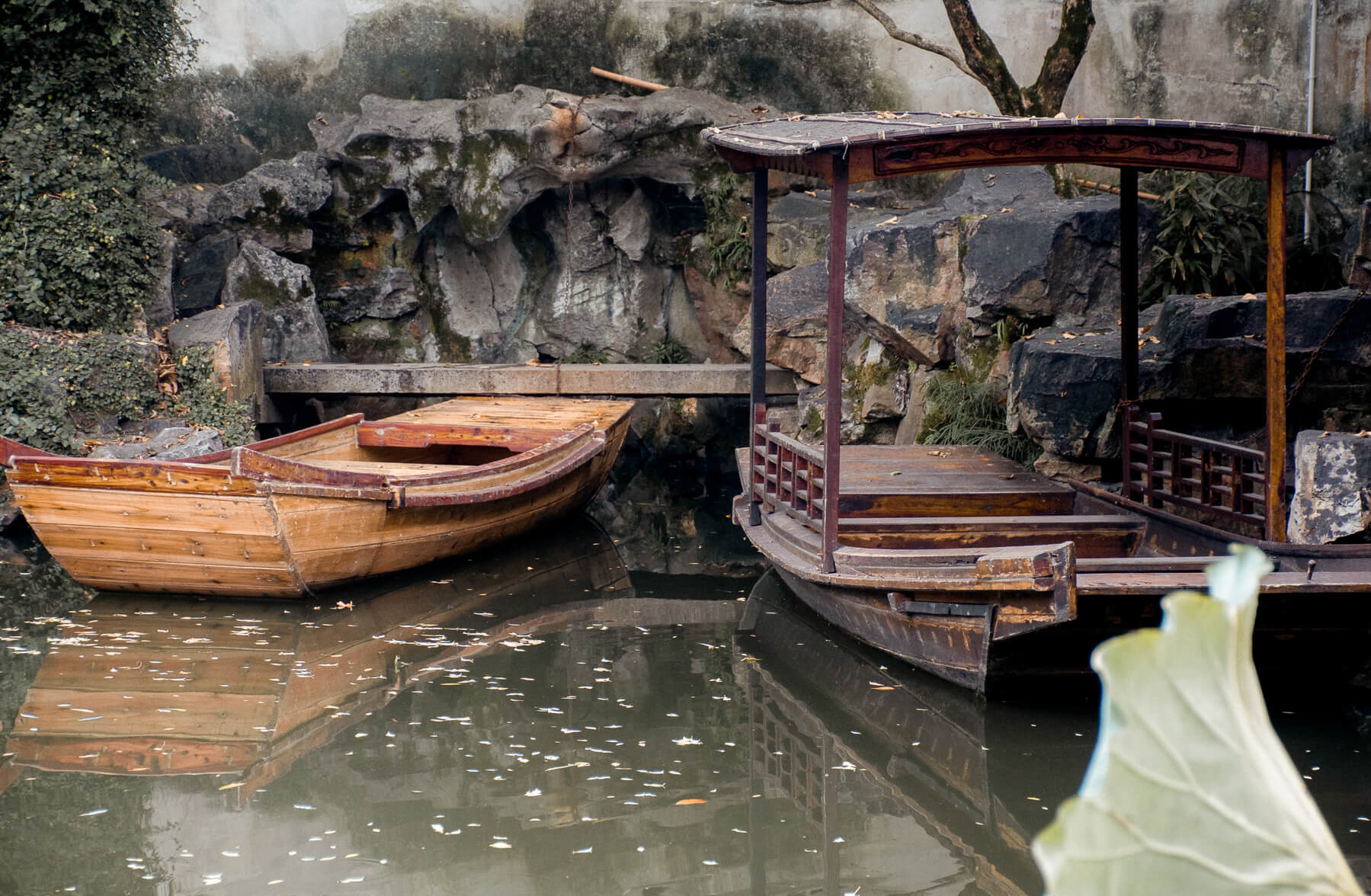 2 old chinese boats against a stone wall in the Lingering Gardens pond