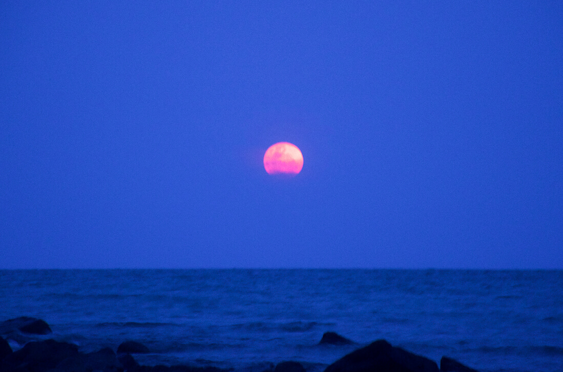 A bright red moon rising over the dark horizon