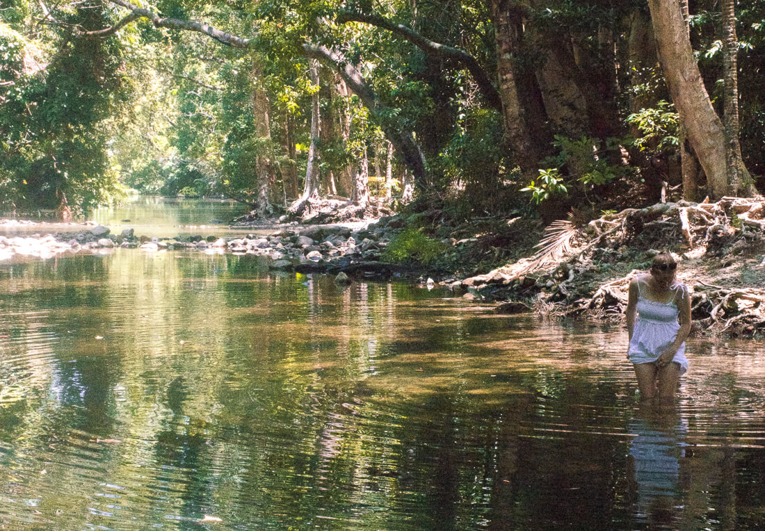 Girl walking knee deep in a river at Cape Tribulation