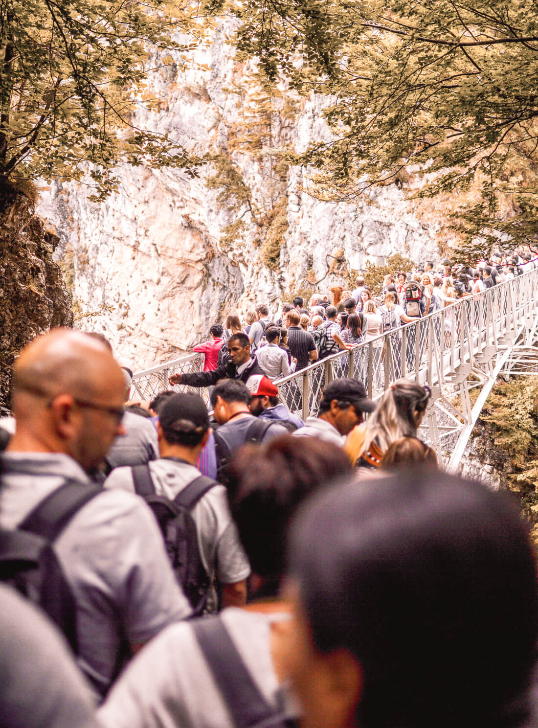 Huge crowd of tourists walking across a tiny bridge