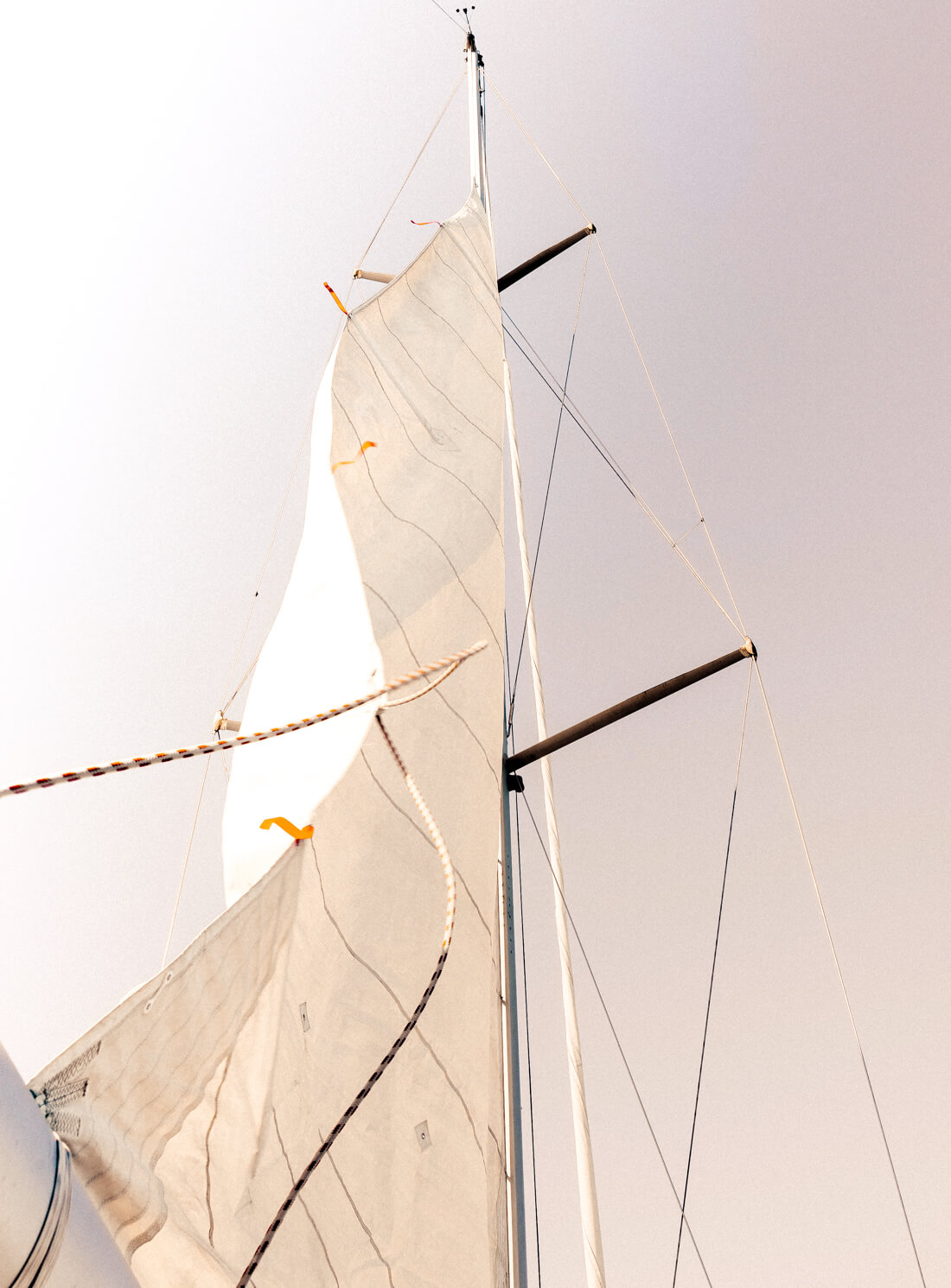Looking up at the sail of a sail boat in the sunshine