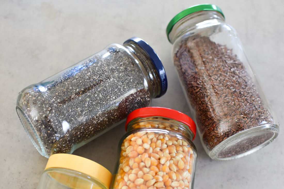 4 glass jars laying on a bench filled with grains and seeds