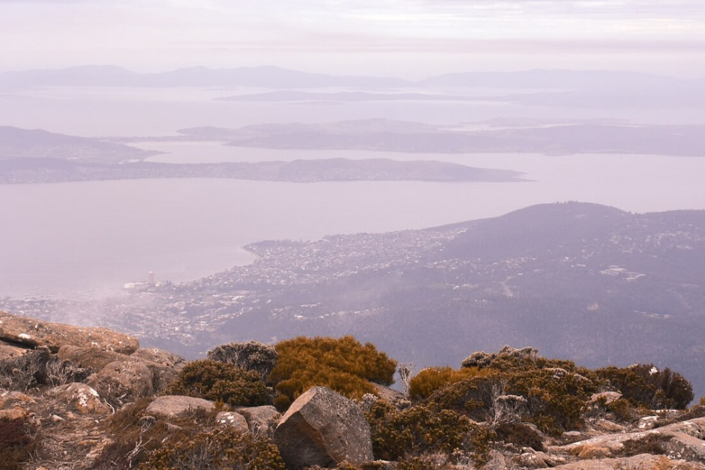 View from a mountain peak overlooking bays and Tasmanian landscapes below