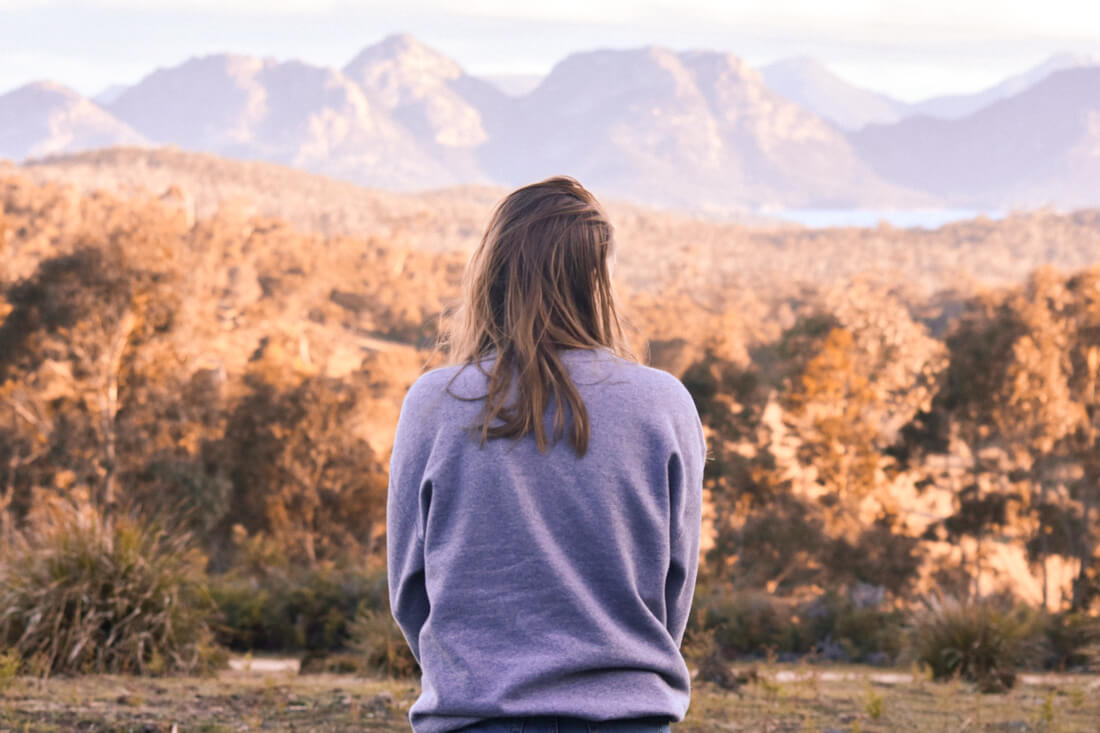 Red haired girl overlooking mountains and bush in Freycinet National Park