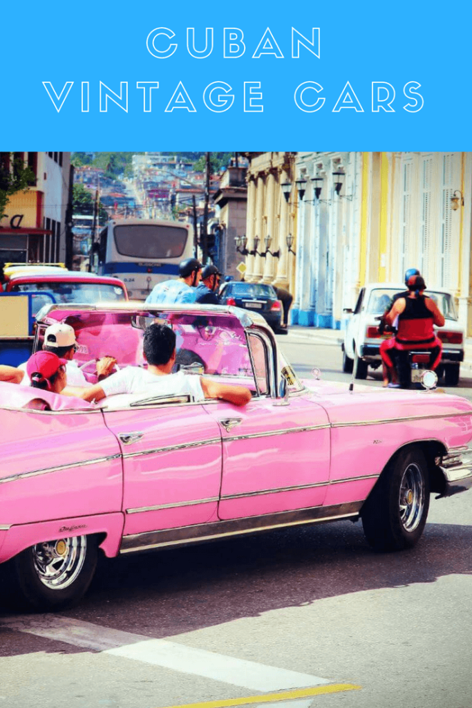 Picture shows a  pink vintage car in the streets of Cuba