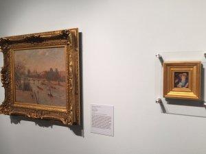 A small portrait by Renoir next to a Pissarro cityscape at Cornell Fine Arts Museum.
