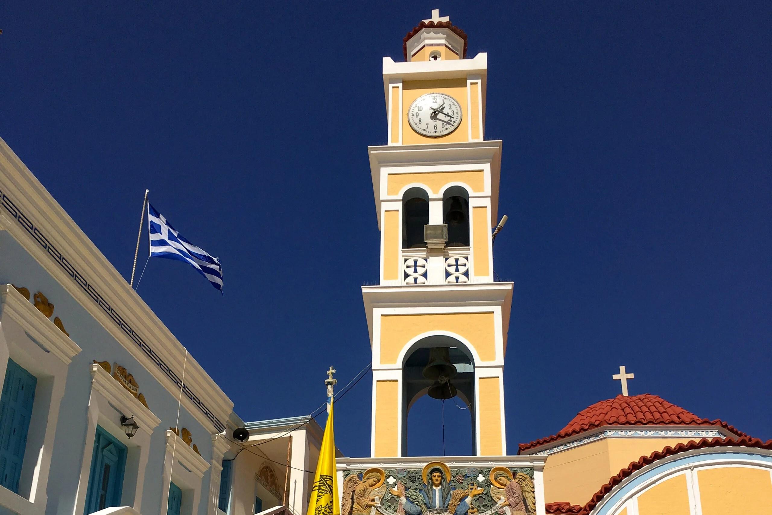 campanile di colore giallo di una piccola chiesa con una bandiera della grecia che sventola
