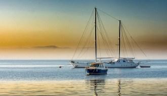 una barca a vela ferma in mare al tramonto