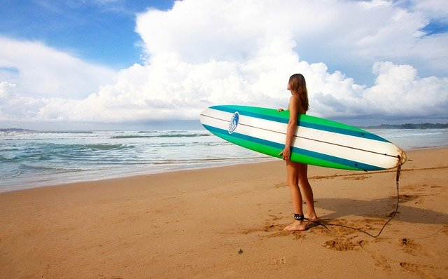A girl with wakeboard at beach on vacation