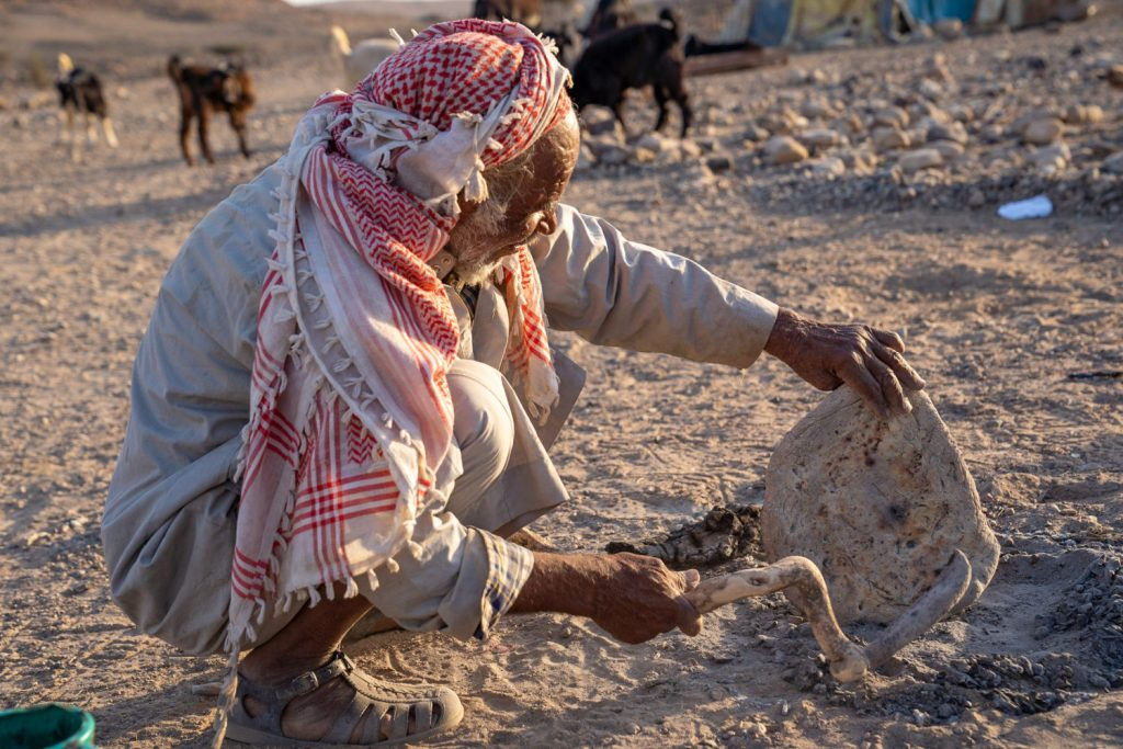 Bedouin finishes the bread that he prepared for guests, near Dana Biosphere Reserve, Wadi Arabah, Jordan, image by Marie Goff
