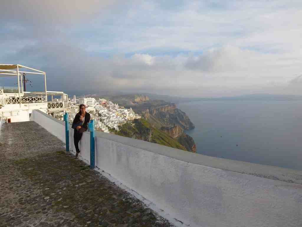 girl standing in the streets of Santorini, Greece at sunset with white houses