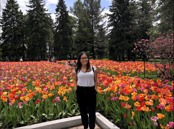 girl with brown hair and glasses posing in front of tulips at the montreal botanic garden