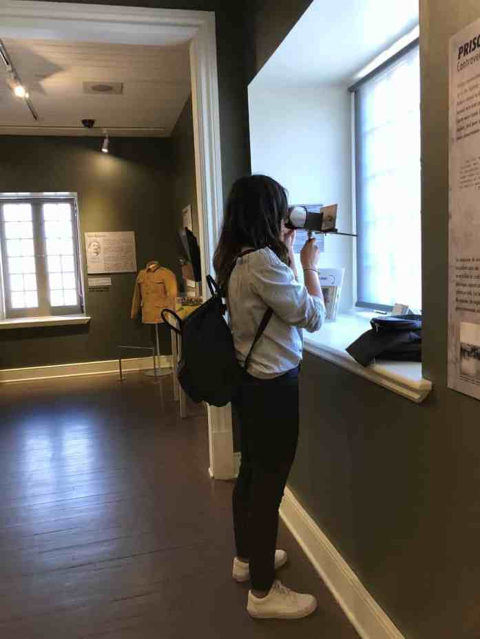 Girl looking through binoculars at museum