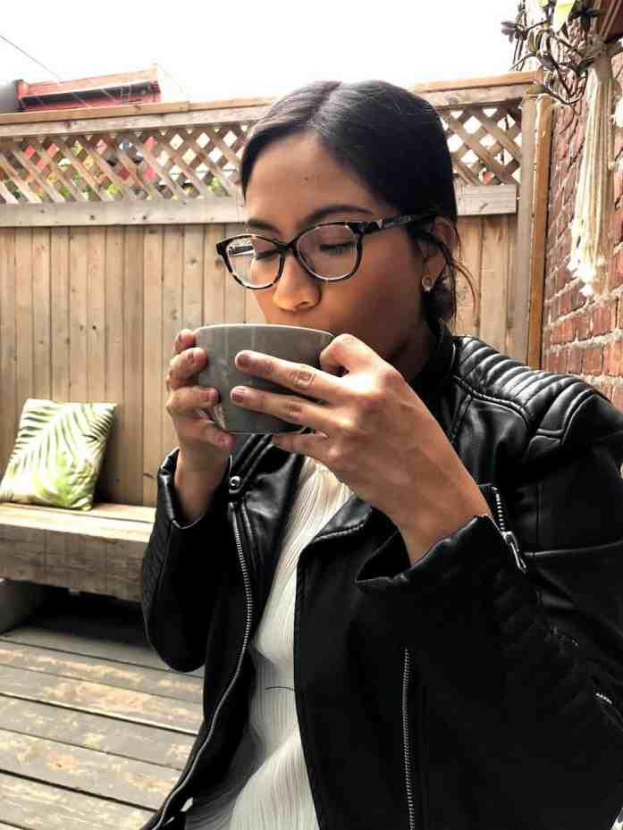 girl with glasses drinking a cup of coffee