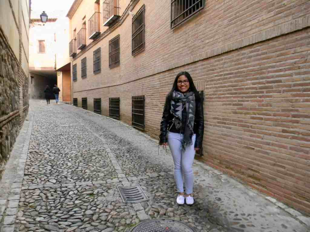 girl in black jacket and light wash jeans posing in a cobble street in a Spanish town Toledo, Spain.