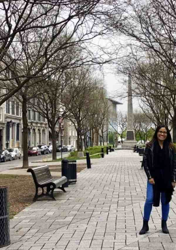 girl in black jacket and blue jeans standing in Montreal, Canada street