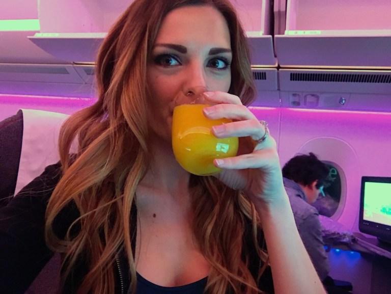 Kashlee Kucheran drinking orange juice on Qatar Business Class flight