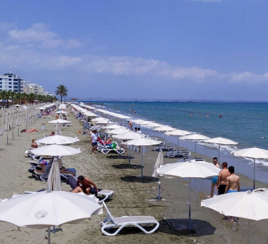 tourists with umbrellas on beach in cyprus