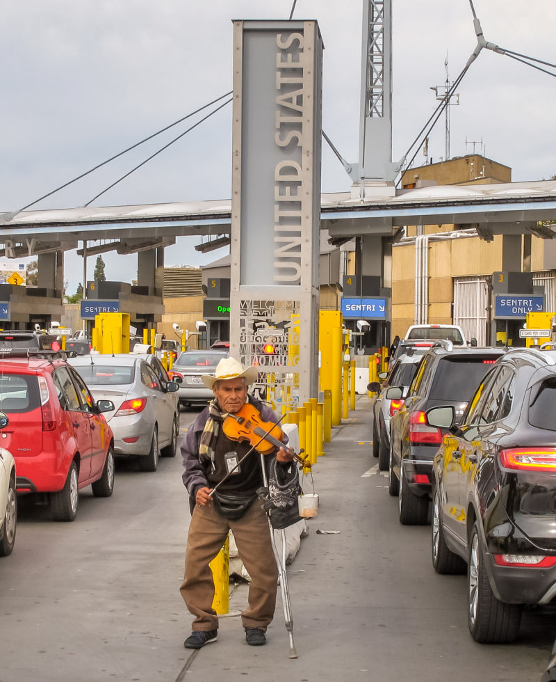 An elderly person plays his violin among the dozens of cars queued on the Mexican side waiting to cross the border into the United States prio to the pandemic
