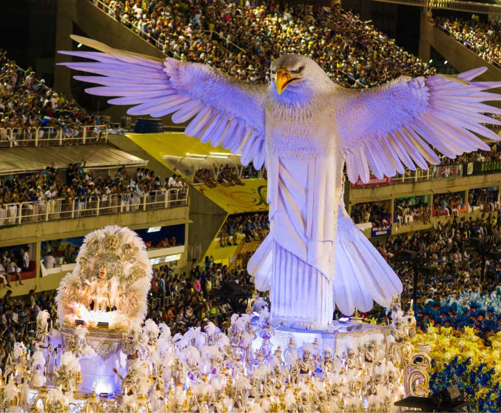 Women participating in Samba Parade are dancing samba on top of lavishly decorated parade float. All participants are wearing elaborate costumes.