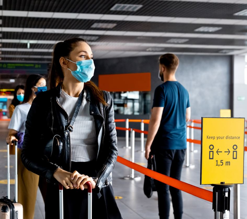 traveler with mask waits in line airport