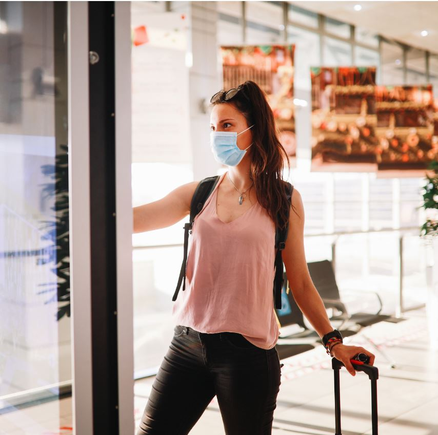 passegner using touch screen wearing mask at airport