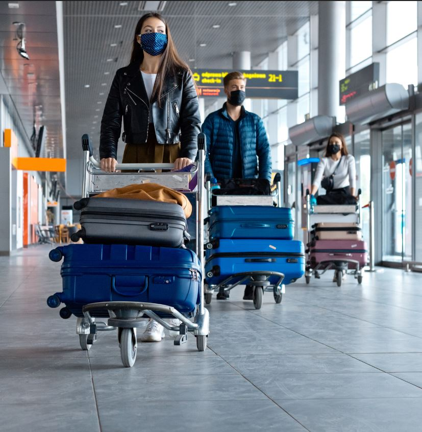 uk travelers with luggage wearing masks