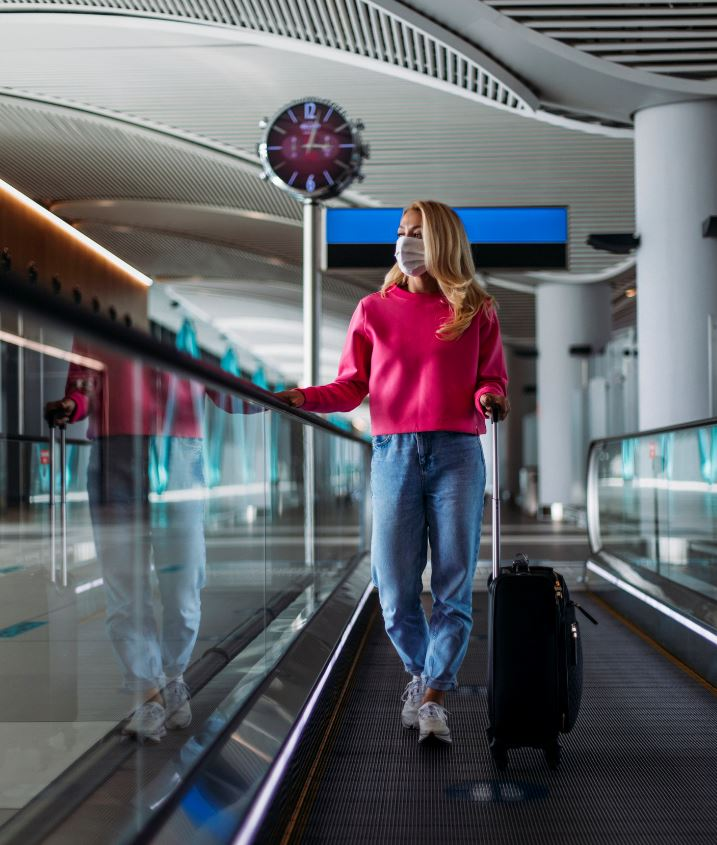 Woman at airport wearting mask with luggage