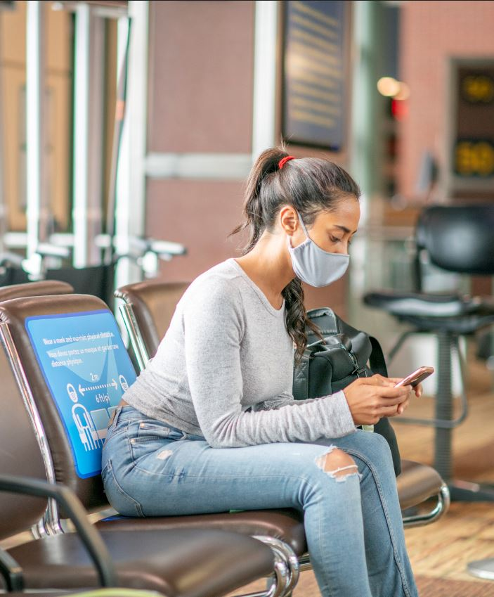 traveler at airport on phone wearing mask