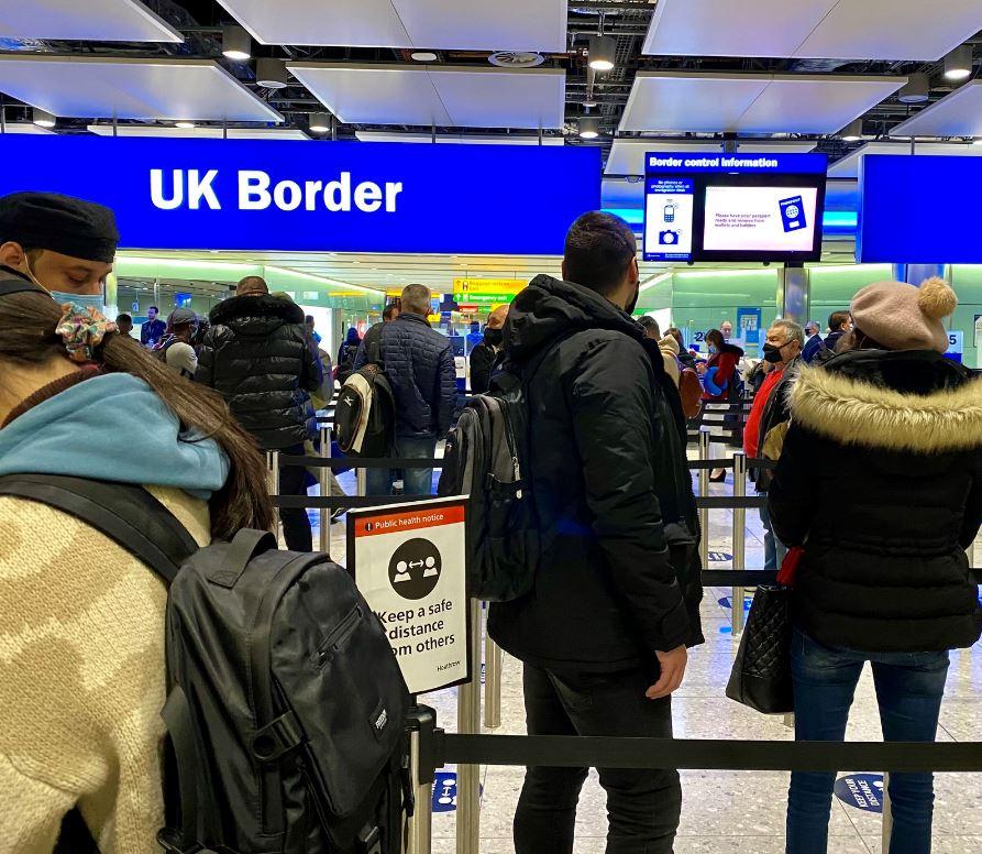 travelers wearing masks queue at uk border control