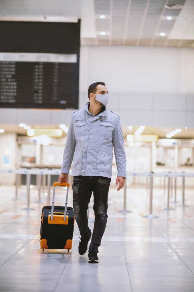 male travelers with luggage and mask at airport
