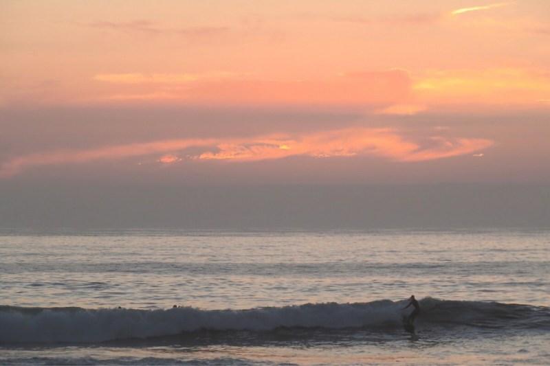 Surfer an der Küste von Nordchile bei Sonenuntergang