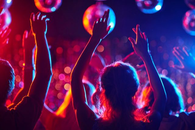 Group of young people with raised arms dancing in night club