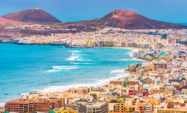 View on the colorful city, promenade, beach and mountains of Las Palamas de Gran Canaria on a late afternoon