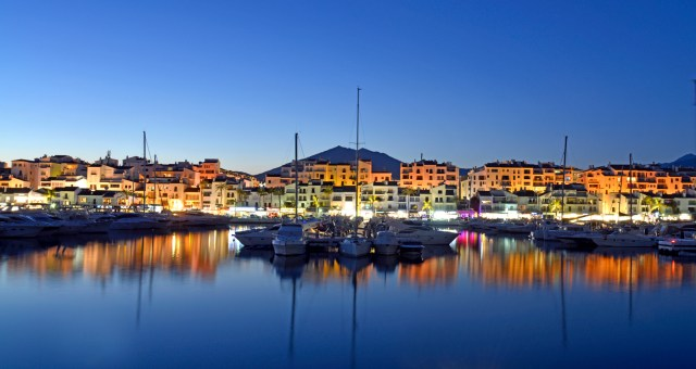 Puerto Banus Marina at night time. Taken just after sundown on a clear evening and showing some of the many boats reflected in the calm water. Beyond are some of the many shops bars and restuaraunts on the busy marina.