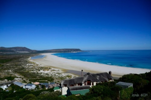 Noordhoek Beach with the suburb, Kommetjie, in the distance