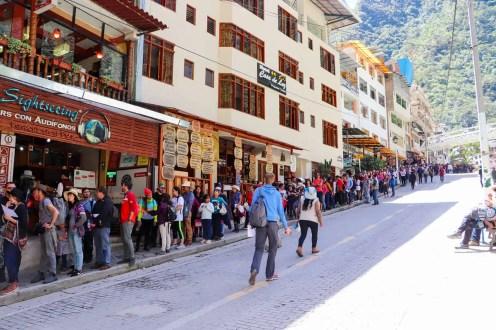 Touristen warten auf die Busse in Aguas Calientes