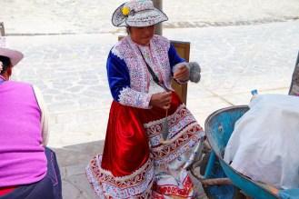 Frau spinnt Alpakawolle mit Spinnrad
