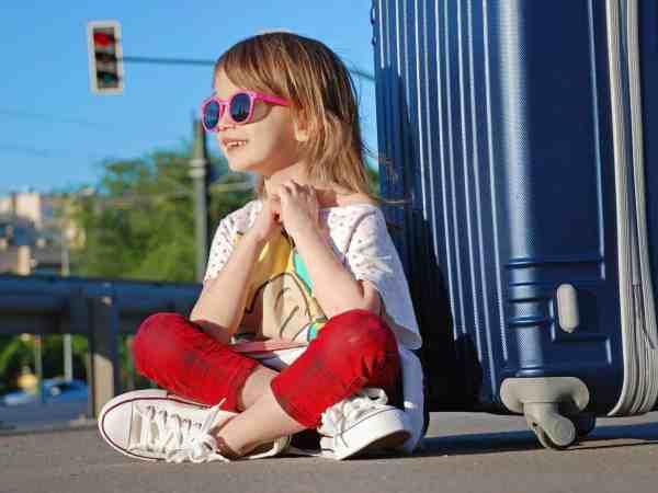 Kind sitzt vor Hartschalenkoffer am Gehsteig