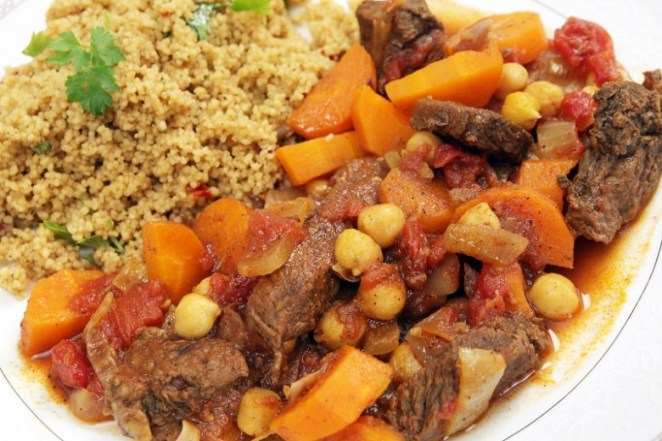 Plate of traditional Moroccan beef tagine with couscous, garnish