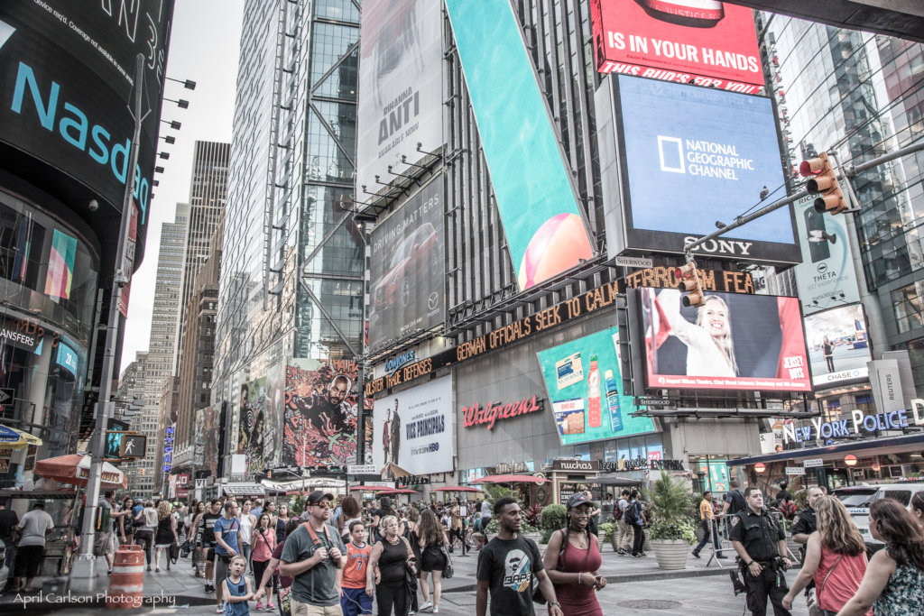Many people walking down the crowded streets of Times Square in New York City which is a great place to visit