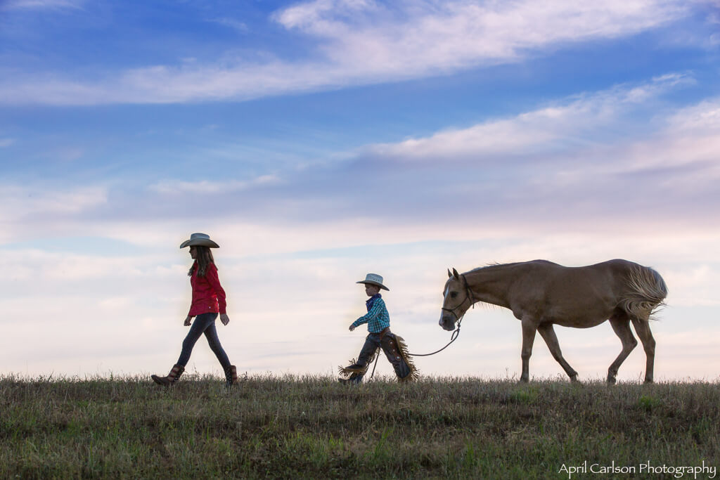 Horse Photography Workshop: Girl and boy walk across the ridge with their horse behind them