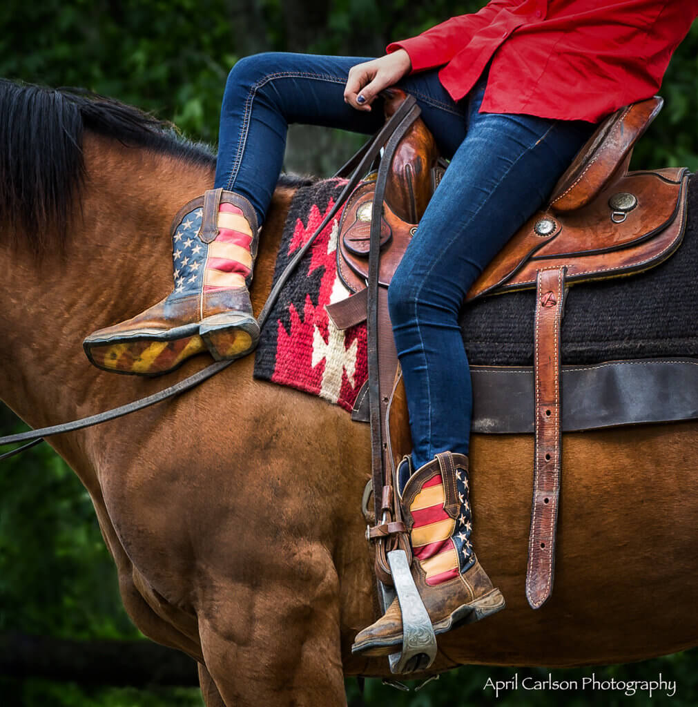 Horse Photography Workshop: Detail shot of Cowgirl in red, white and blue boots on a horse