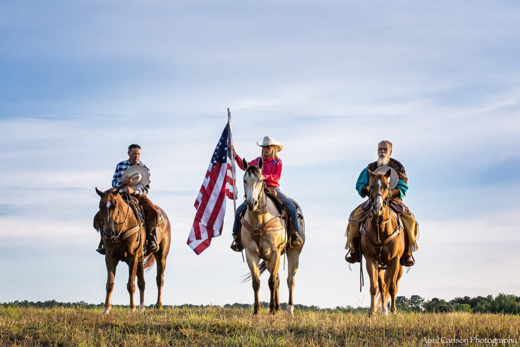 Horse Photography Workshop: Two cowboys and a cowgirl salute the American Flag