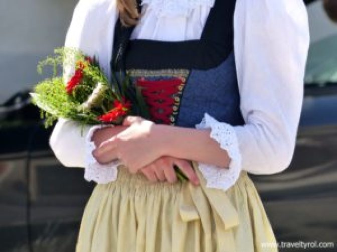 A member of a town band in Austria carries with flowers in her arms.