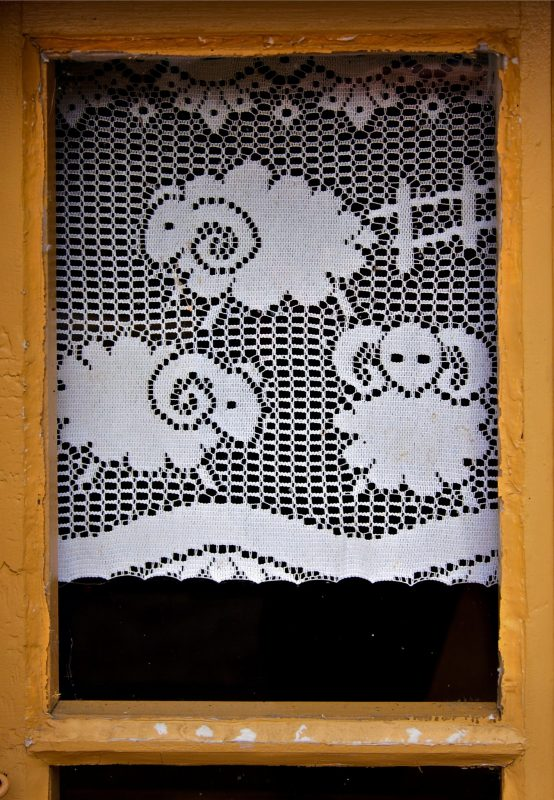 Pastoral lace curtain framed in a window in Quebec