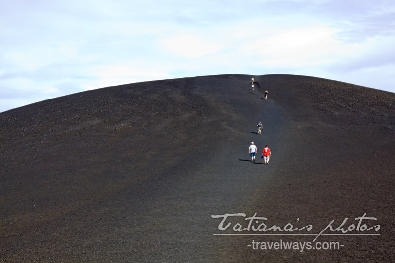 People climbing a lava/ash formatted hill