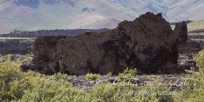 Huge boulder of dark petrified lava in the middle of the field