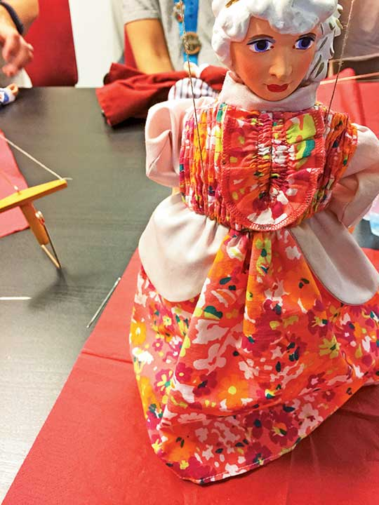 Adventures by Disney tour participants make marionette dolls in Prague.