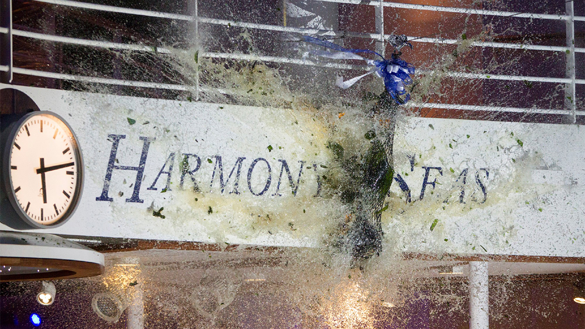 A 3-foot bottle of champagne smashes into the Harmony of the Seas.